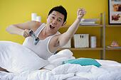 Man sitting in bed,  holding video game remote control,  arms ...